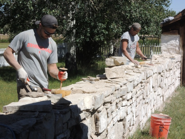 Workers from Wattle and Daub Contractors repair a stone wall at Ft. Bridger in southwestern Wyoming.  Several of the stone structures were built by Mormons, who occupied the site before 1860.  Historic mortars, which hold the stone structures together, are often lime-based and need repaired and replaced over time.