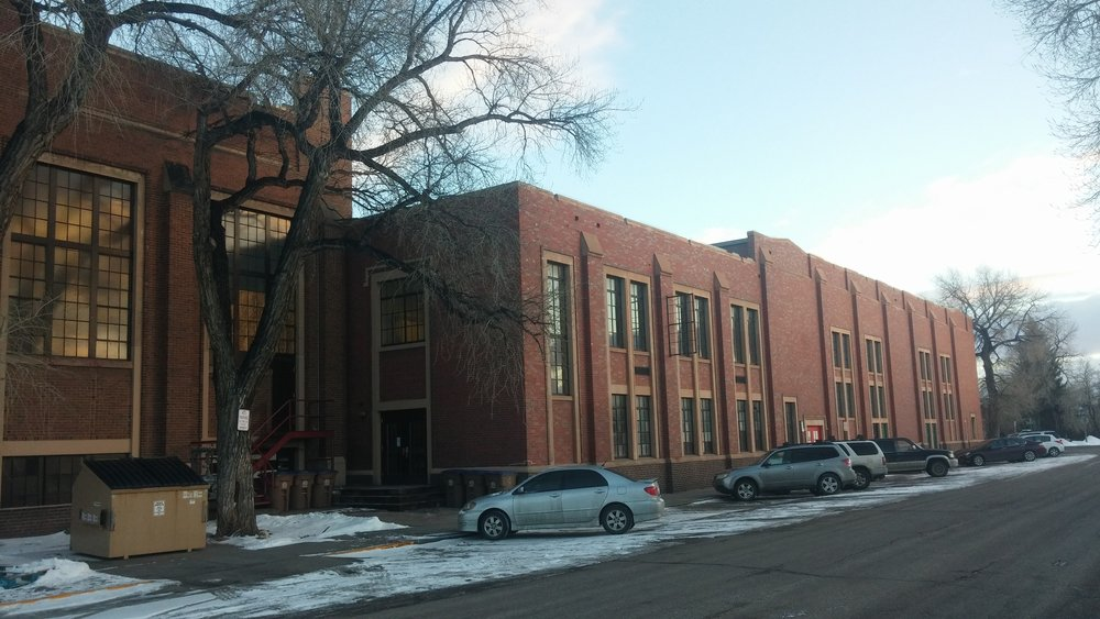 The west facade of the former school shows where two of the large additions converge, with the newer addition to the right and the older addition to the left.