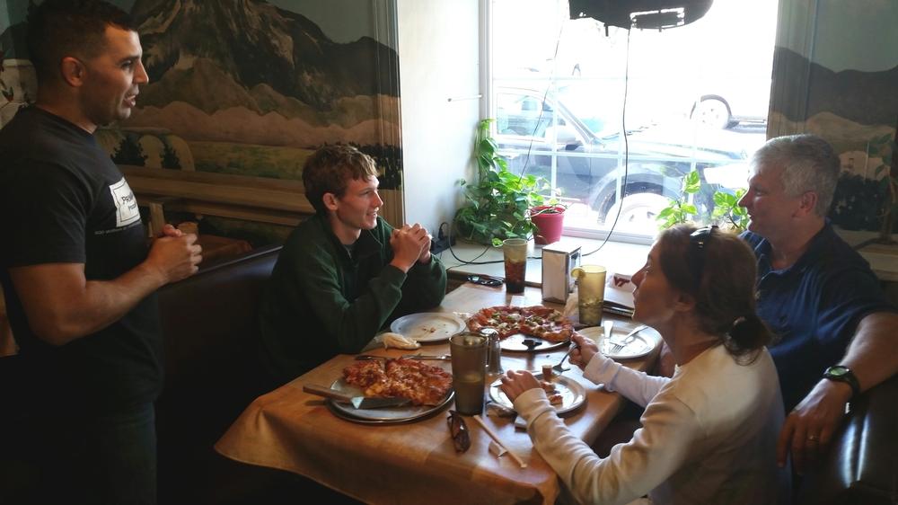Photo by A.E. Bayne - Rami Hamrouni checks on the Platt family as they enjoy their first Primavera pizza.