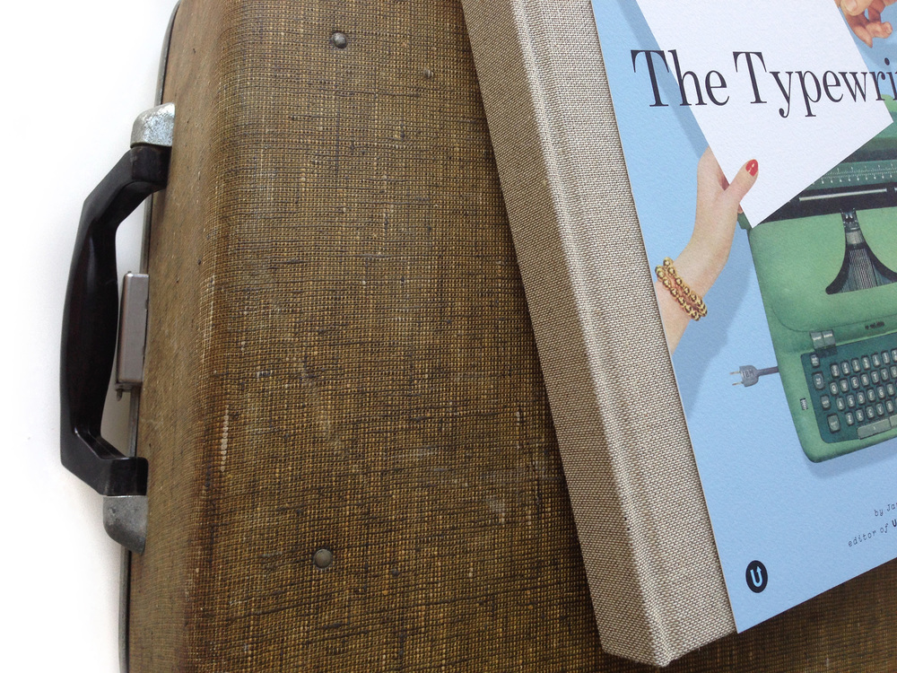 The dark linen cloth spine of the book was inspired by the tweed on a typewriter case from 1956. This photo shows a book mockup; the actual book will have gold foil on the spine where the title and logo will be imprinted.