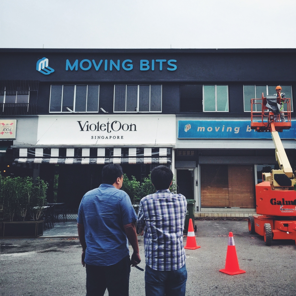 Jay and Ping Nan watches on as our new signage is installed and the old one removed.