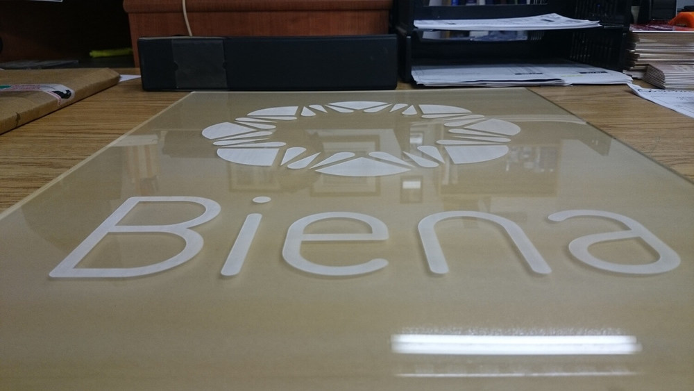 Big sign made out of clear acrylique. The brown hue is given by the protective paper applied to the back of the sign.