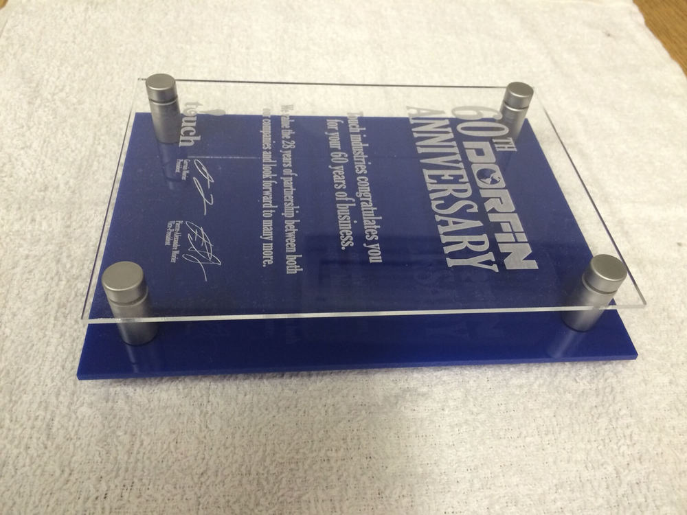 A plaque made with a laser engraved clear acrylic layer and an underlying blue acrylic layer