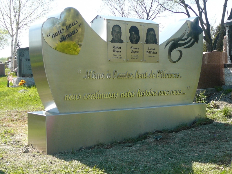 A large gravestone with letters, photos and drawings made with laser engraving.