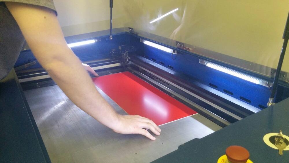 Plaque lamicoide rouge en train d'être placée dans la graveuser lsaer