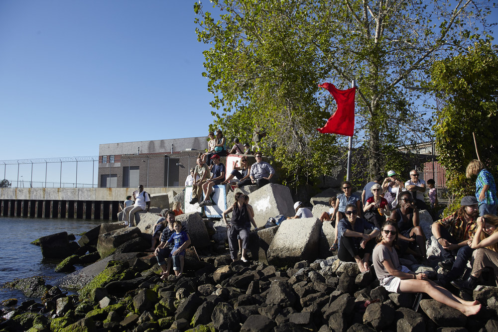Crowd on the Red Hook blocks and flag by artist Azikiwe Mohammed