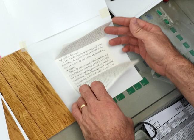 hands holding open a handwritten letter