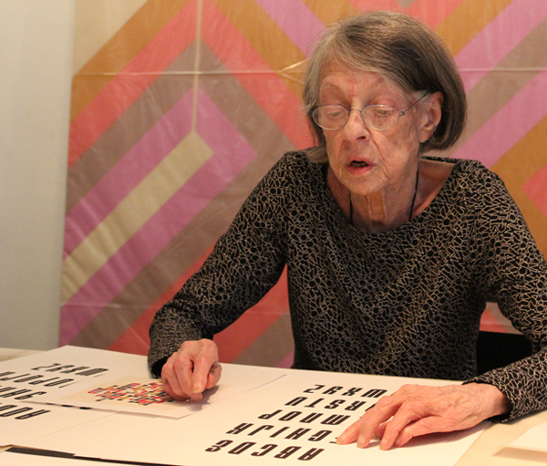 Old woman examining an alphabet printed in black letters on white paper