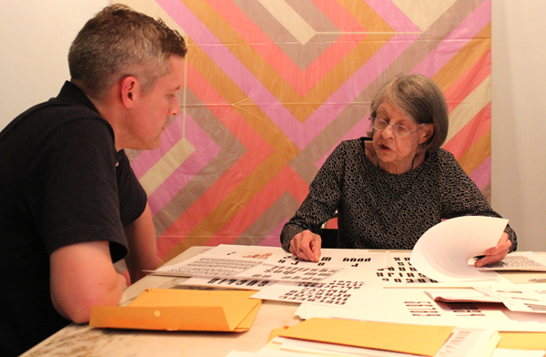 Old woman and young man examining a typeface