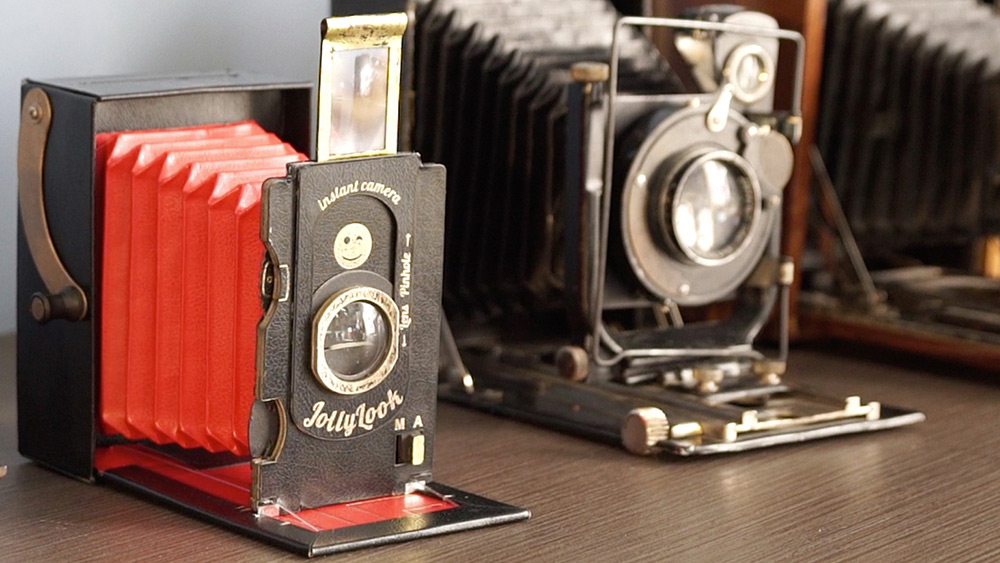 Two old accordion-like instant cameras