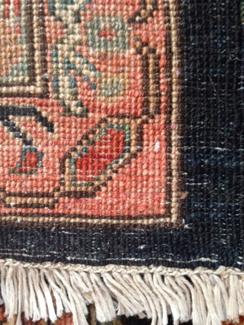 Reverse side of a hand-knotted carpet. Note imperfections in knotting, clarity of the rug design, and fringe as part of the rug construction.