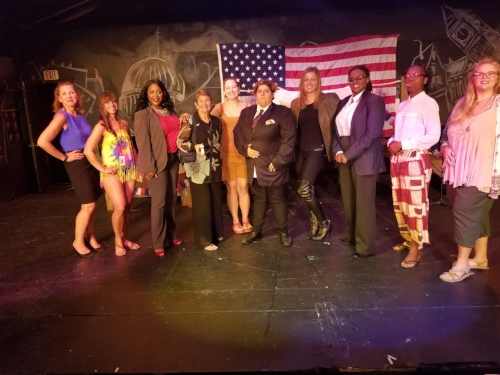 "Cast of the most recent Whodunnit ""The Body Politic"" written and directed by actor Julie Baber, standing center in gold"