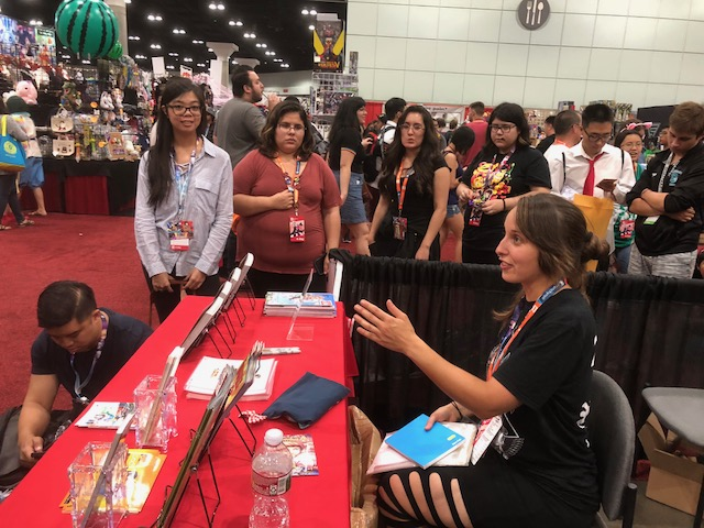 Signing books for fans at Anime Expo