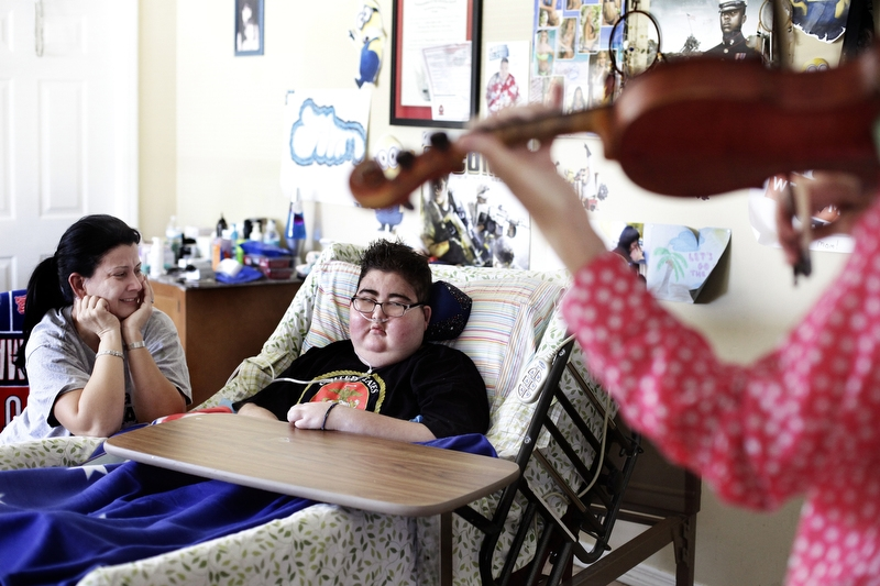 "Maria Maldonado and Ethan Arbelo, 12, watch as violinist Nanette Grant plays a private concert on June 12, 2014 in Lehigh Acres, Fla. ""I'll do anything to get his spirits up,"" Maria said."