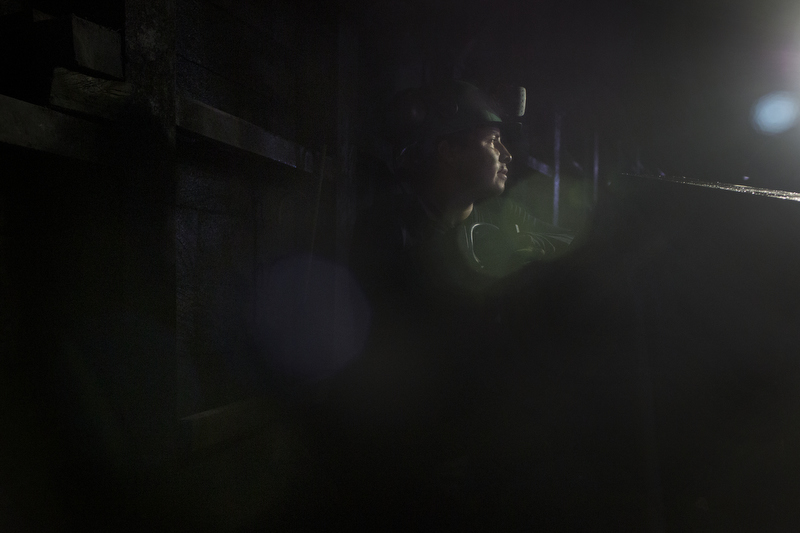 Julian Martinez stands by as a mining utility vehicle drives into place inside an emerald mind owned by Minería Texas Colombia in Muzo, Colombia, on July 24, 2015. Miners work on 8-hour shifts on a run of 20 days on followed by 10 days off.