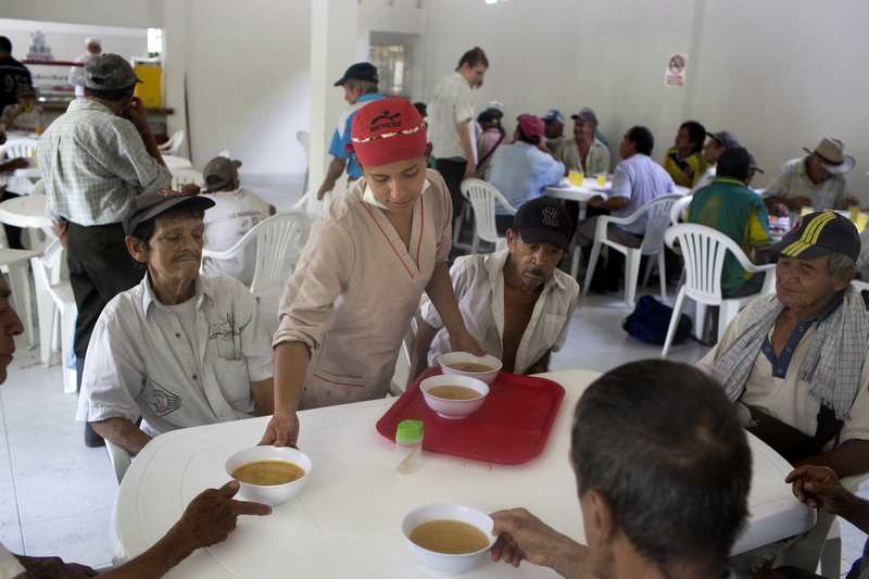 Karen Dicelis serves soup at the community eatery, El Mirador de los Abuelos, during lunch in Muzo, Colombia, on July 24, 2015. El Mirador de los Abuelos is one of the social investments made by Minería Texas Colombia to provide one free meal a day to the elderly.