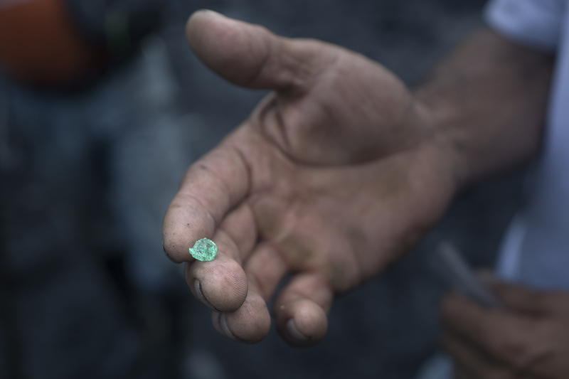 Independent emerald mine laborer, Efrain Sanchez, displays an uncut emerald he found sorting through the dirt and rubble tossed out by Minería Texas Colombia plant in Muzo, Colombia, on July 26, 2015. Apart from the rare chance that they strike big, informal emerald miners usually make between 100,000 to 200,000 pesos a month, about 35-70 dollars.