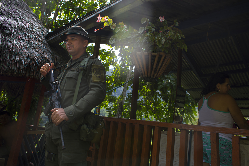 Colombian National Police officer Francisco Gomez patrols the area near the Minería Texas Colombia plant in Muzo, Colombia on July 26, 2015. Forero started patrolling the area shortly after the mine was invaded in May 2015.