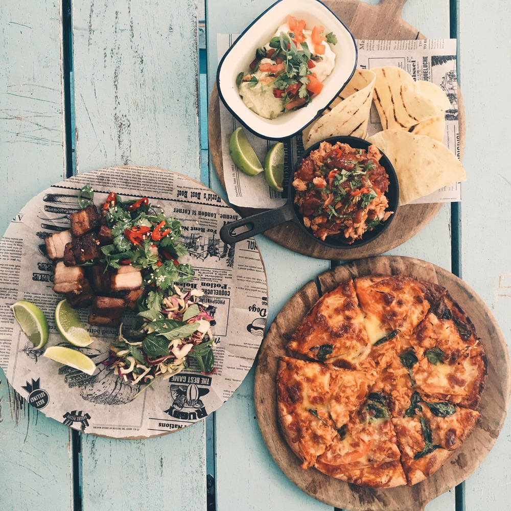 Clockwise: Shredded chicken tacos, Peri Peri chicken pizza, pork belly bites