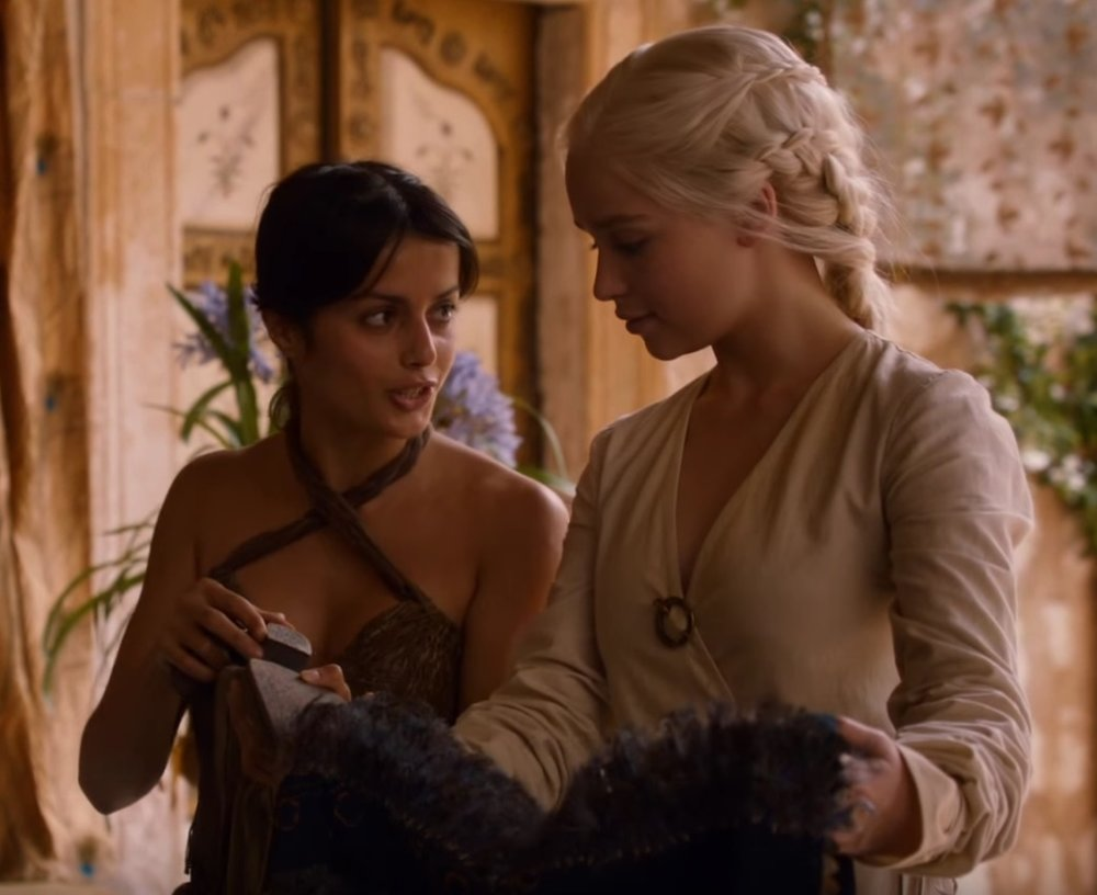 Dothraki lady-in-waiting Irri shows her khalessi how she has repaired her shoes and clothing.