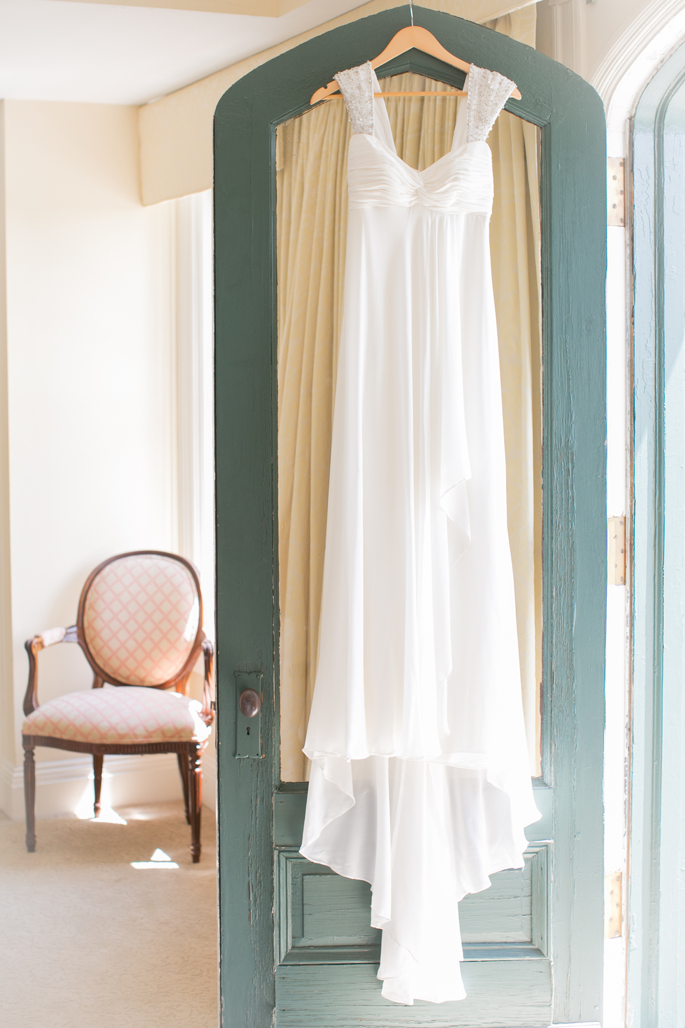 The bride's dress hanging in her dressing room