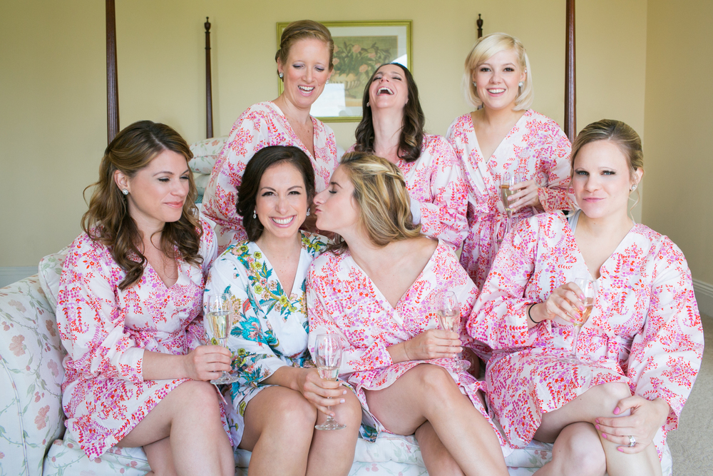 The bride and her bridesmaids all celebrating and getting ready for the wedding