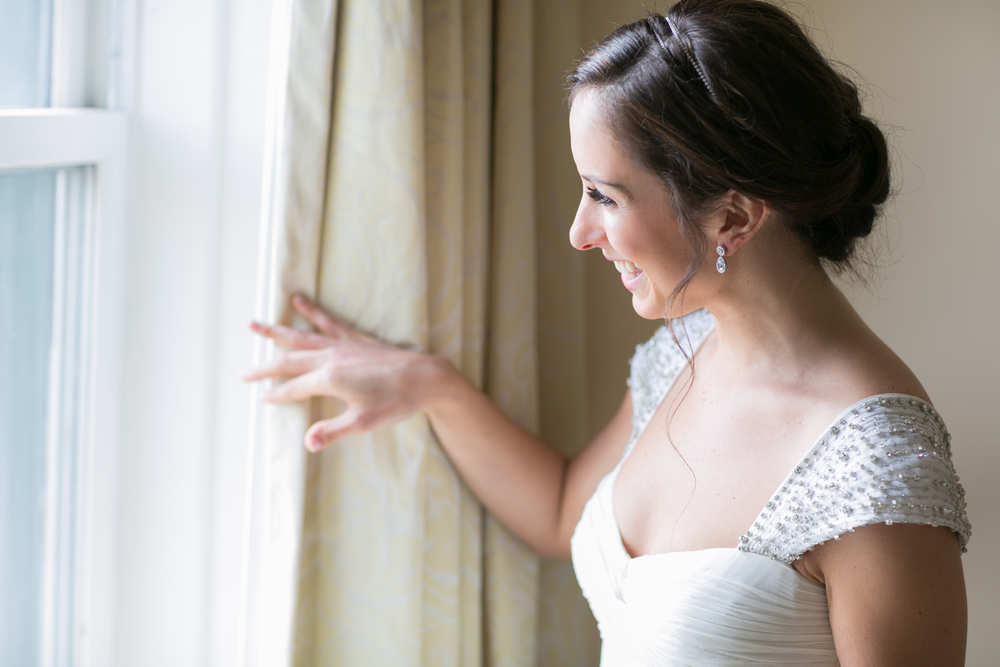 The bride looking outside her window to see her groom