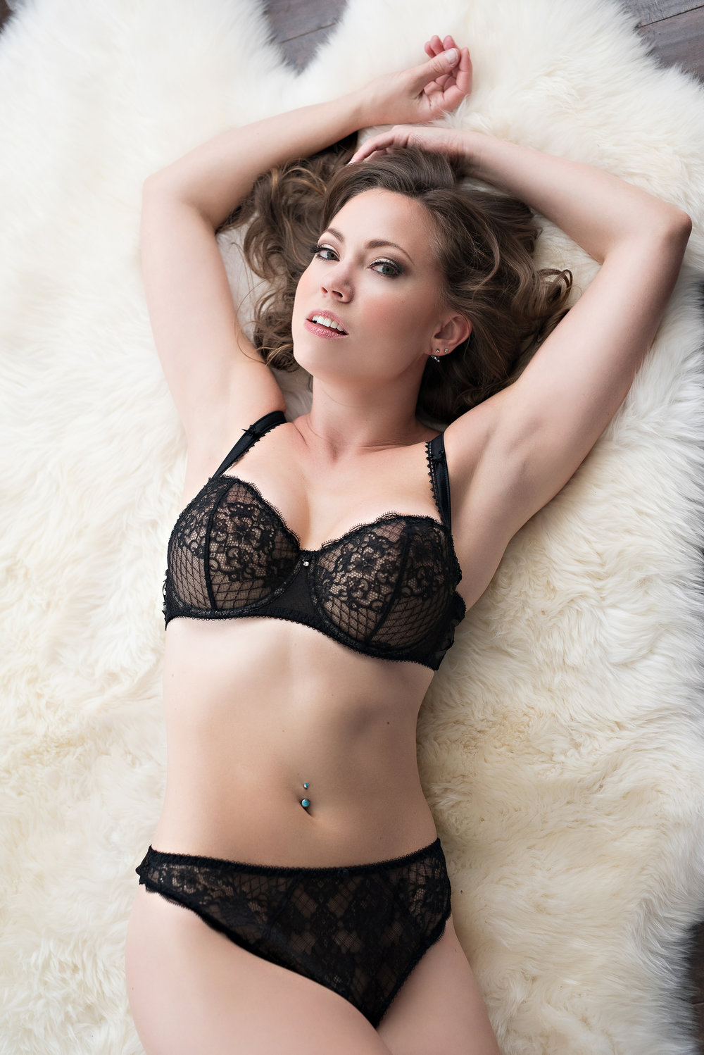 fit woman smiling in boudoir pose Denver Colorado photographer
