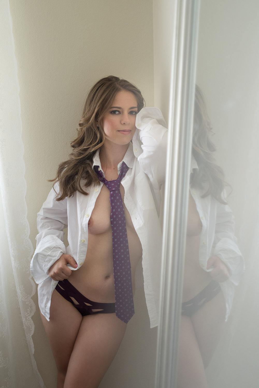 Colorado boudoir photography session of brunette woman wearing unbuttoned shirt and purple tie
