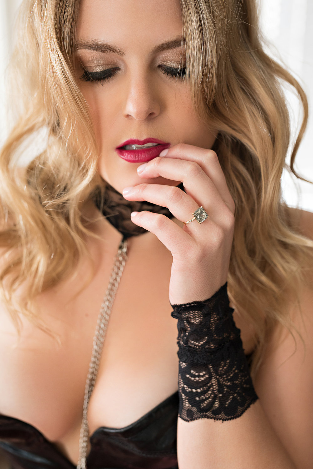Blonde woman with sensual expression wearing black lingerie Denver boudoir photoshoot