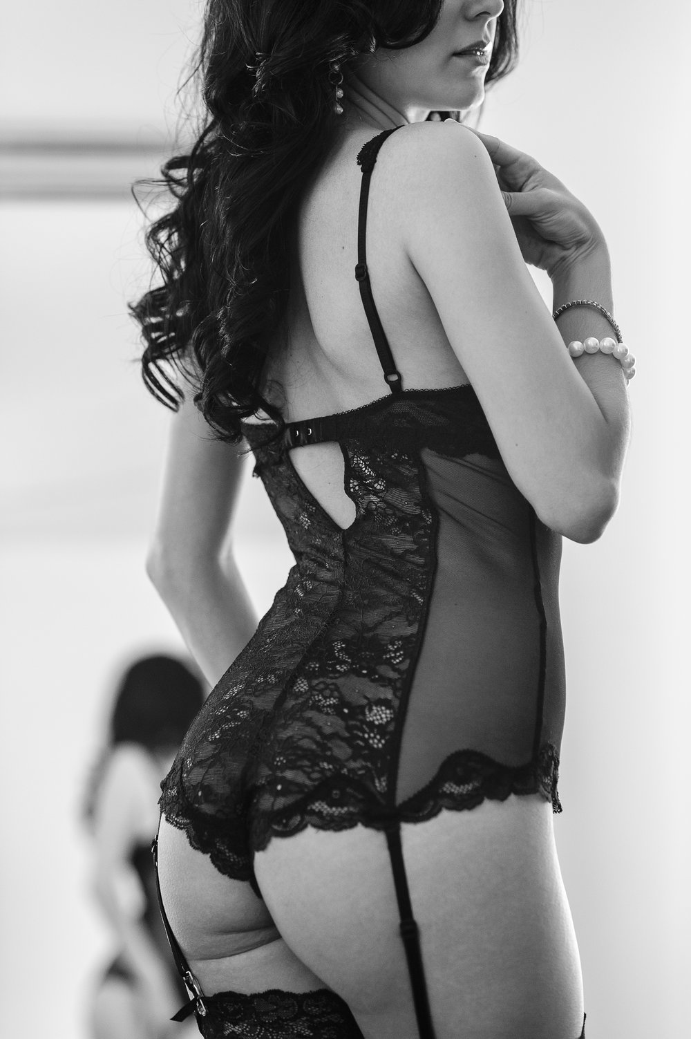 Woman wearing black lace lingerie in boudoir pose