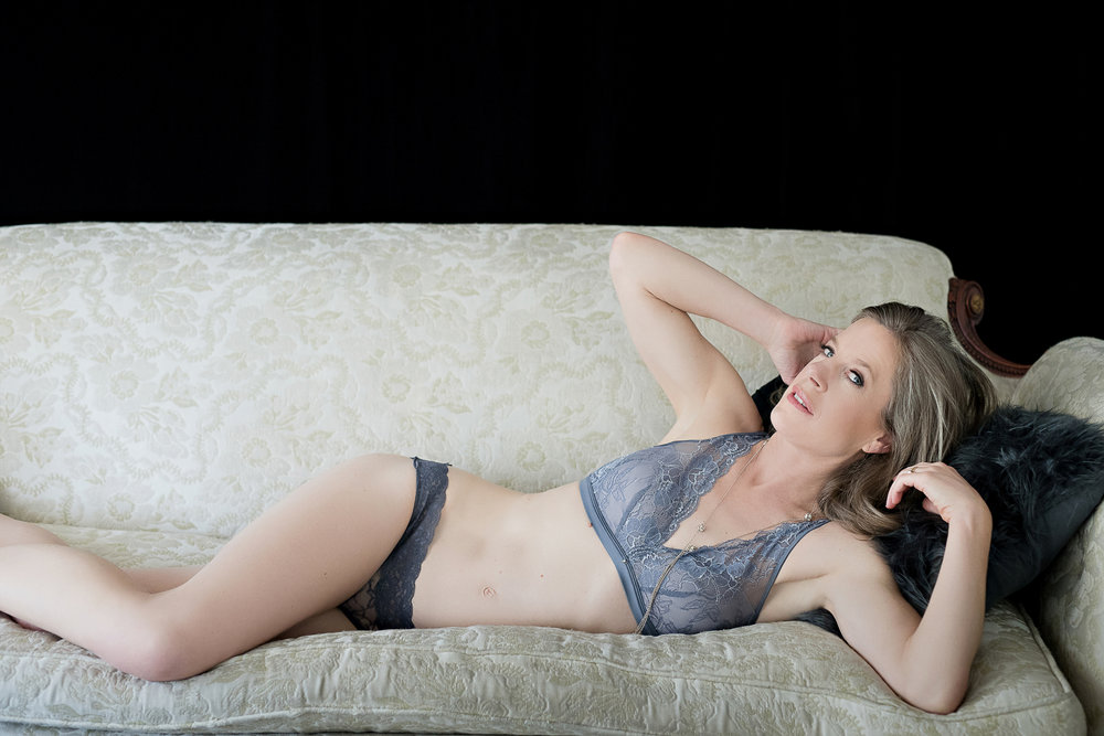 Older woman wearing lingerie laying on couch in boudoir pose Denver photographer