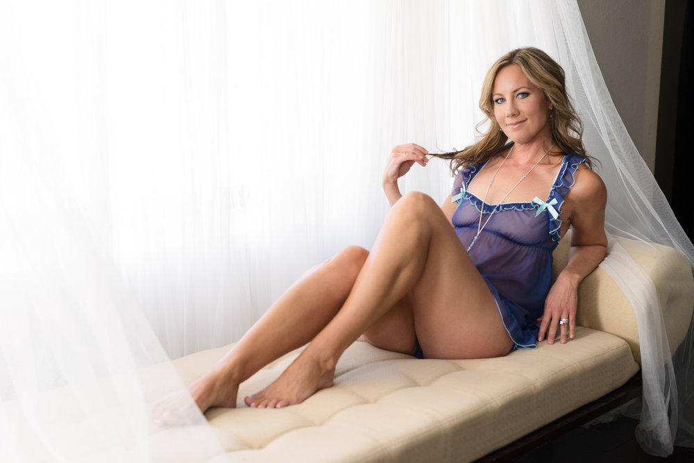 Intimate photo of woman in purple lingerie coyly smiling