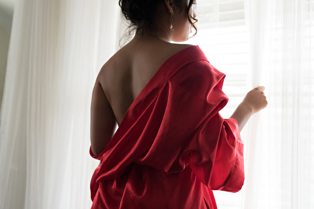woman of color wearing red robe in vintage inspired boudoir session Denver photography studio