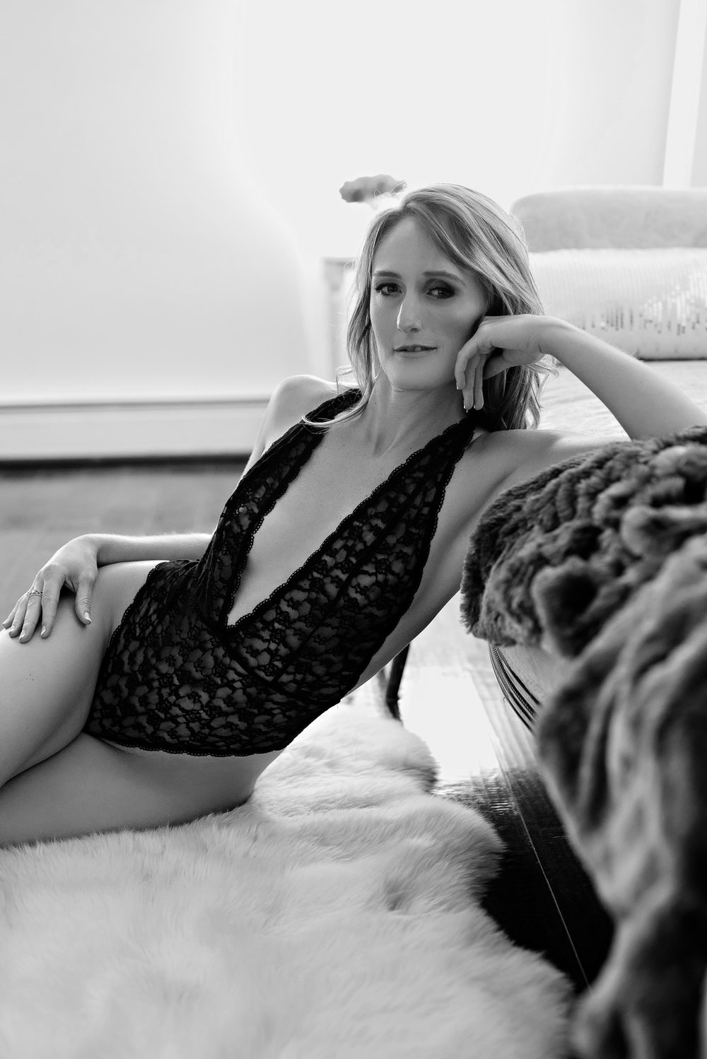 Woman wearing black lace bodysuit in black and white boudoir photo
