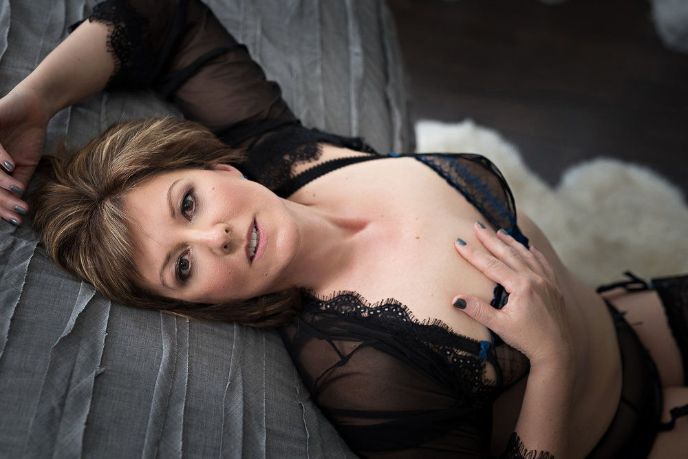 Older woman with sultry look wearing black lingerie Denver boudoir photography