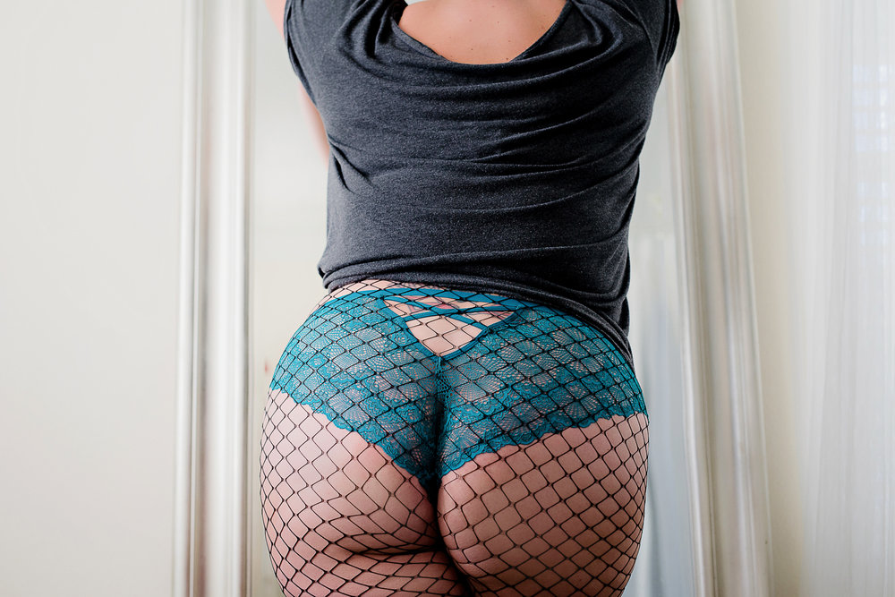 Denver boudoir photo of plus size woman wearing fishnet stockings