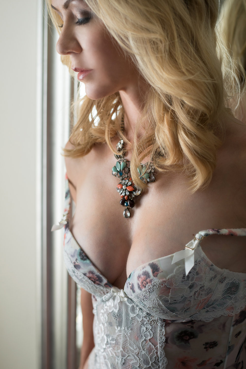 Blonde woman wearing floral lingerie in Denver boudoir studio