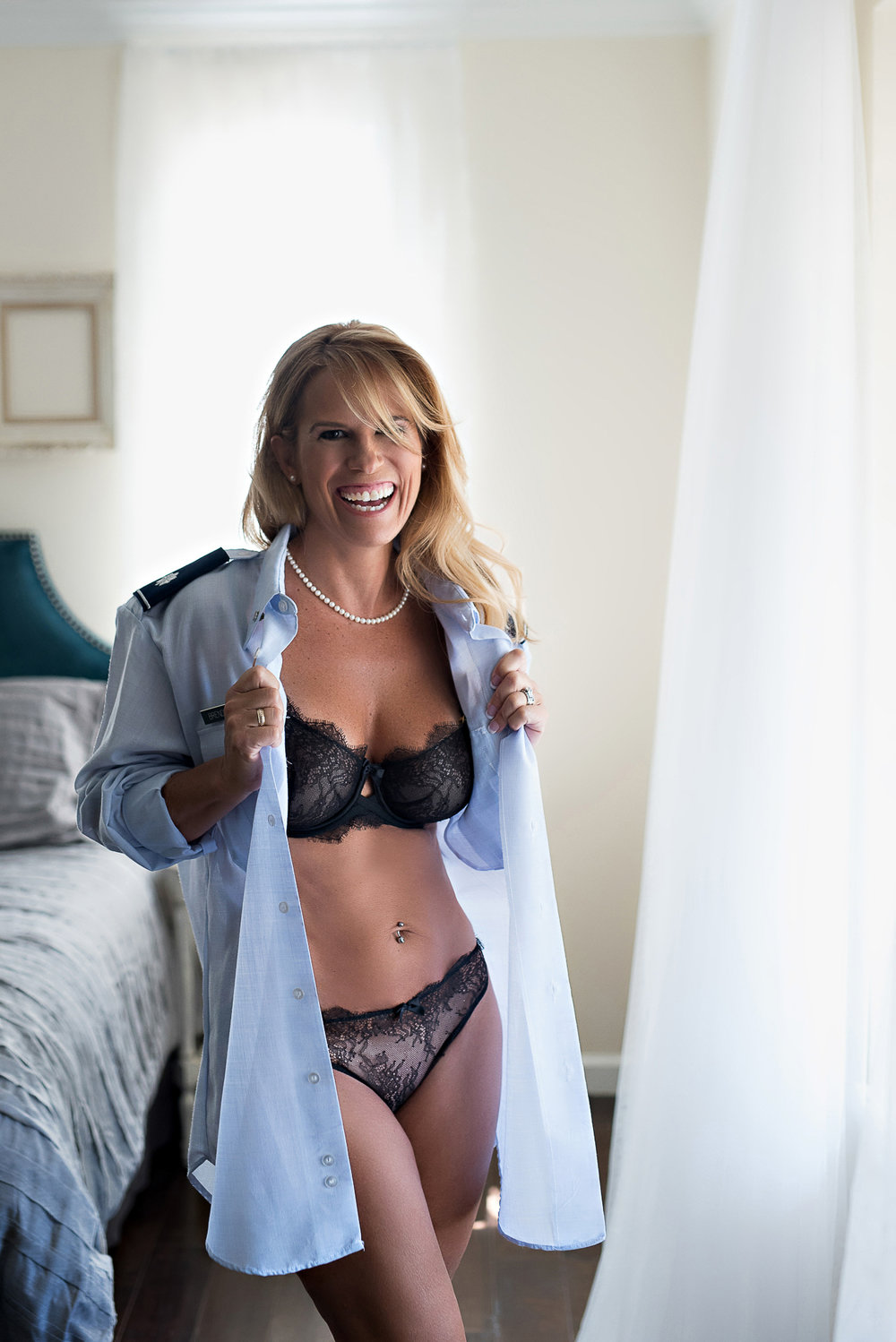 Denver boudoir photographer picture of  blonde woman wearing unbuttoned blue shirt and black lingerie