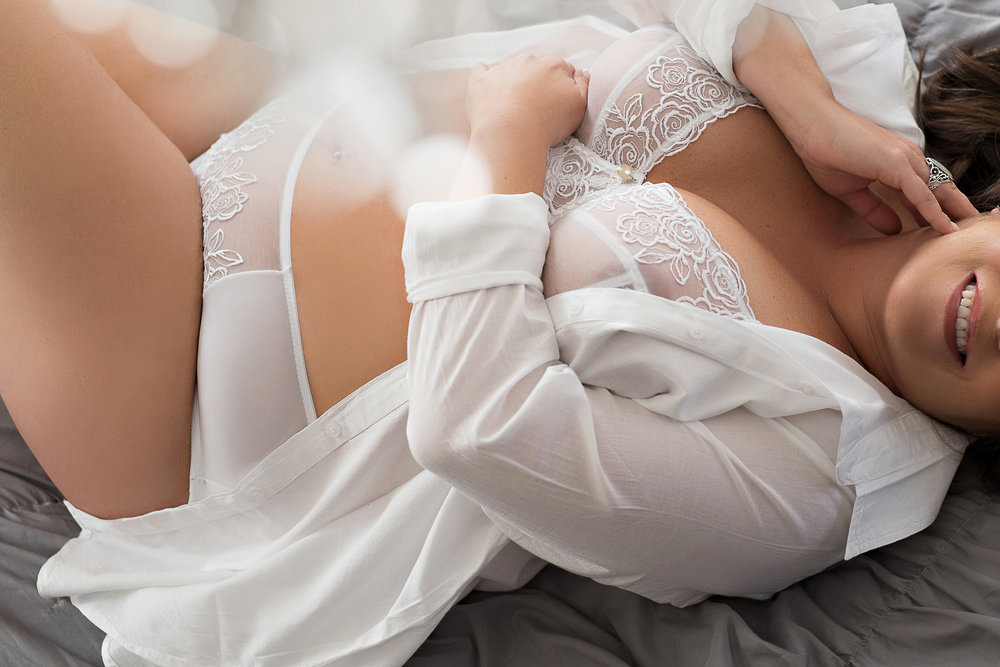 curvy woman in boudoir pose wearing white