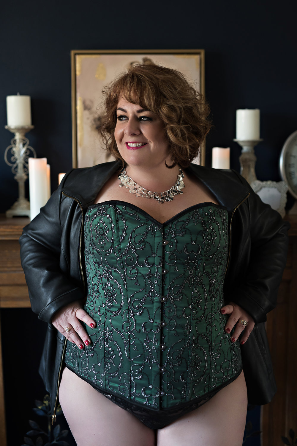 Denver boudoir photo of plus size woman in green corset and leather jacket