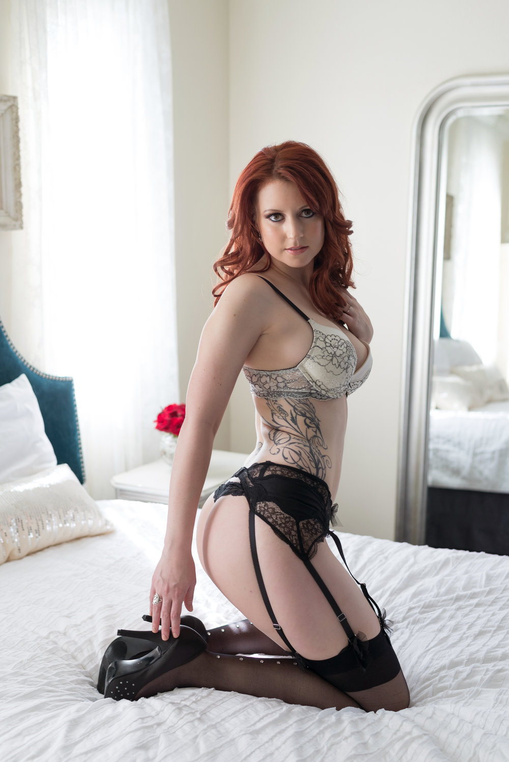 woman with red hair and tattoos in boudoir pose Denver intimate portraits