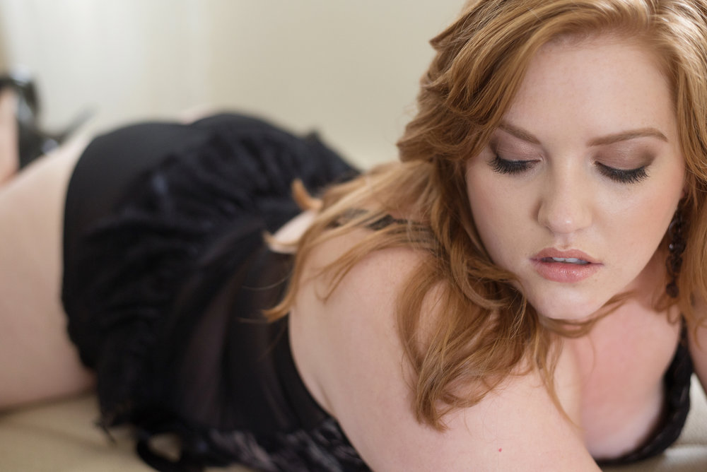 Curvy redhead wearing black lingerie in Denver boudoir photography studio