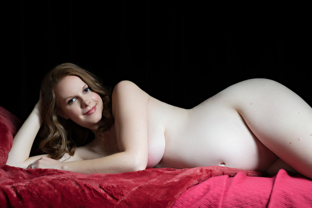 Pregnant brunette laying in boudoir pose on red blanket Denver Pregnancy photographer
