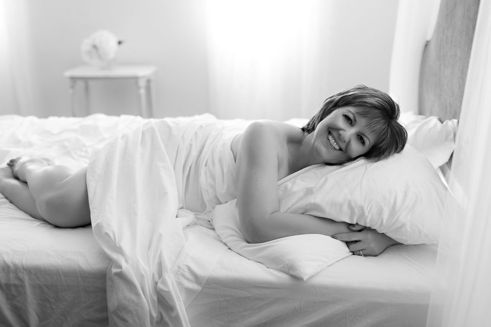 wife smiling inwhite sheets in boudoir photoshoot