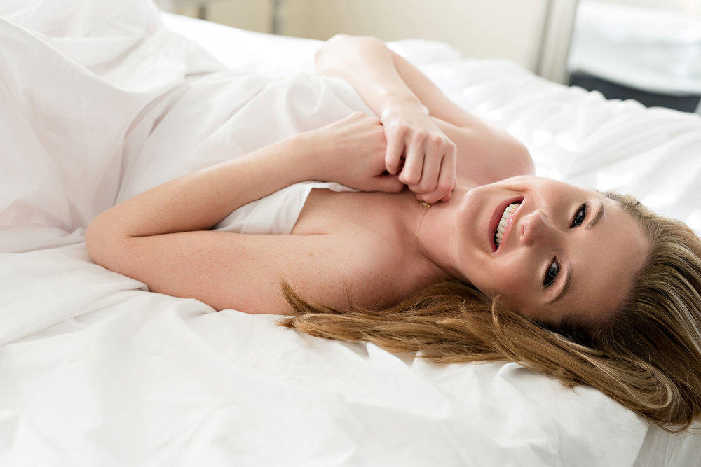 Young smiling blonde woman in boudoir white sheets pose Colorado boudoir