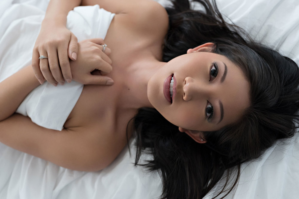 Young Asian woman in white sheet boudoir session at Denver boudoir studio