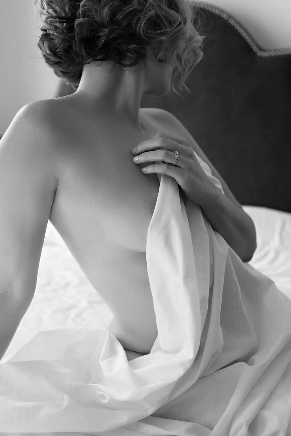 woman in white sheets boudoir session Denver Colorado