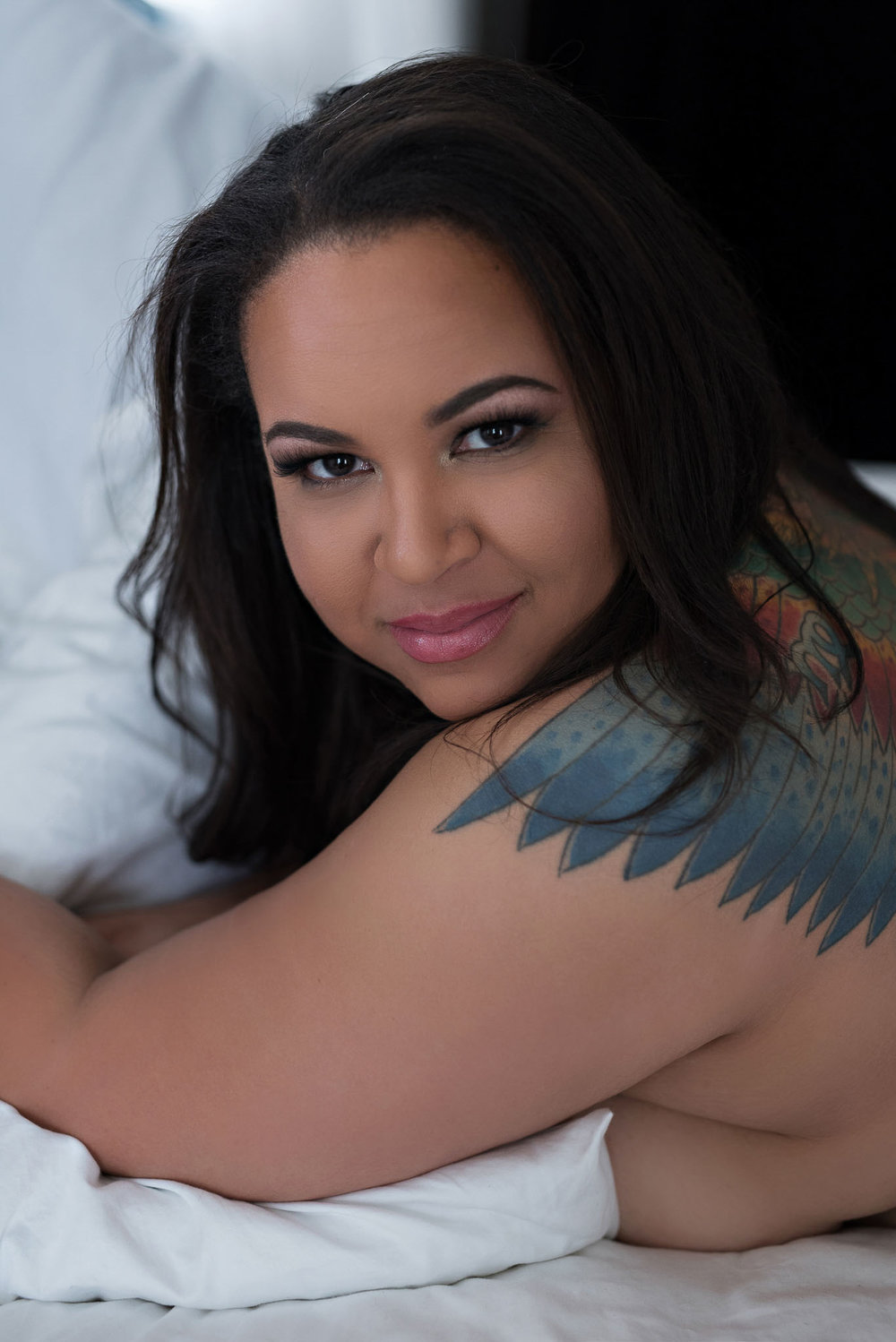 Curvy tattooed African American woman with sultry eyes in boudoir pose Denver photographer