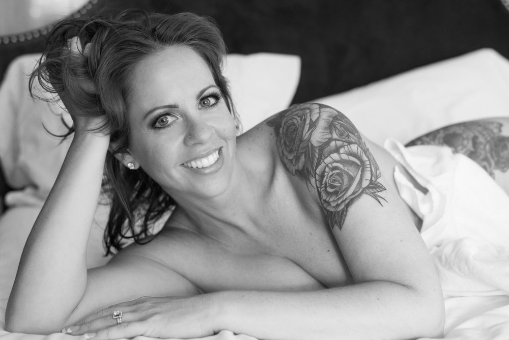 Tattooed smiling brunette in seductive boudoir pose at Denver studio